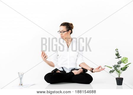 Side view serious woman watching at cellphone while doing yoga exercise. Office concept. Copy space