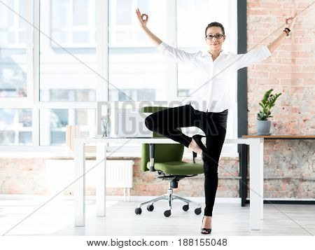 Half length happy woman making exercise at job. She standing in wide modern office