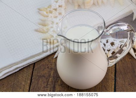 Milk in glass milk jug close up on rustic wooden background with lace jug cover and white kitchen cloth