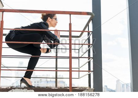 Side view female expressing happiness while doing gymnastics on balcony outdoor