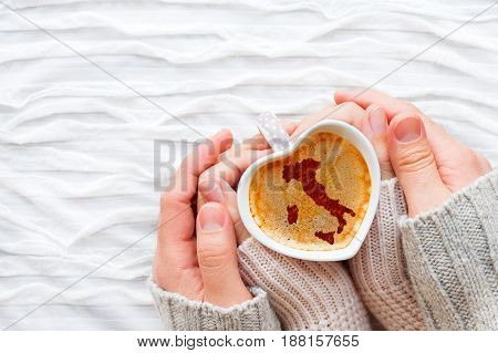 Woman and man holds a cup of hot coffee with cinnamon silhouette of Italy. Winter wanderlust and Valentine's Day fabric background.