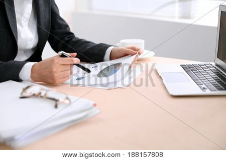 Business woman sitting at the table and examines the financial results.