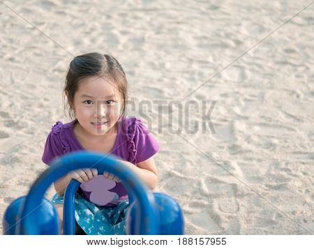 happy Asian child on a seesaw sand background