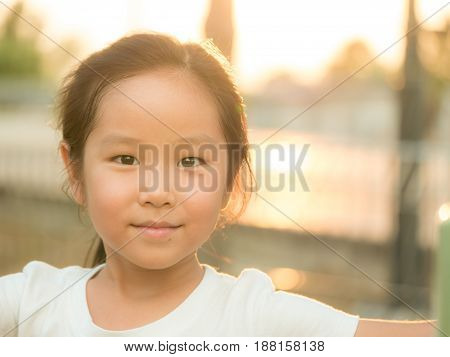 adorable Asian cute girl close up head shot healthy girl sunset light