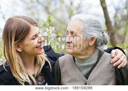 Picture of a happy elderly woman with her cheerful carer outdoor springtime