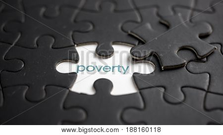 Word poverty under black jigsaw puzzle piece