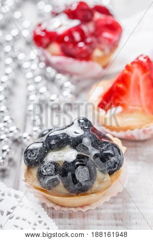 Fruit tarts with berries and strawberry on light background close up. Delicious dessert and candy bar. Top view