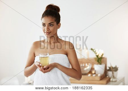 Portrait of beautiful african girl in towel holding glass with tea smiling. Copy space. Spa salon.