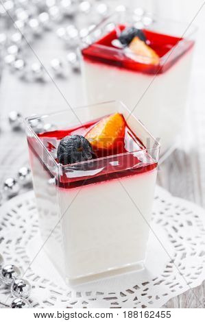 Tasty mousse with jelly and berries in a glass on light background close up. Delicious dessert and candy bar. Top view