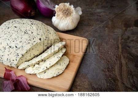 Homemade Organic Cheese with herbs basil on black stone slate background. With copy space