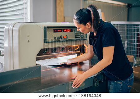 Worker In Printing Centar Uses Paper Guillotine Machine Knife