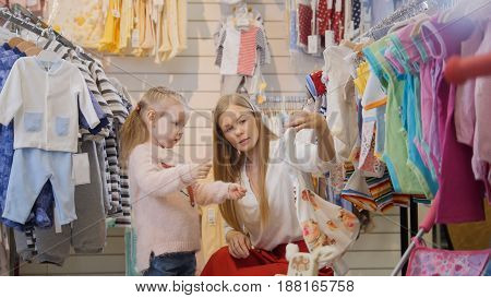 Portrait of a young woman and a little girl. Mother and daughter carefully consider children's summer white dress with floral pattern