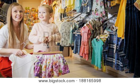 A young mother with a young daughter choose a summer outfit in a clothing store for children