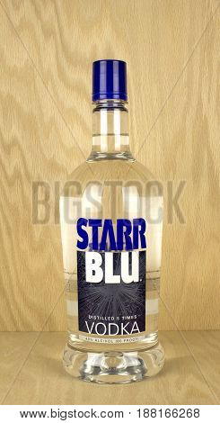 RIVER FALLS,WISCONSIN-MAY 25,2017: A bottle of Starr Blu brand vodka with a wood background.
