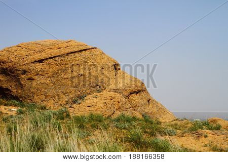 Steppe small rocks of yellow stone with green grass on them
