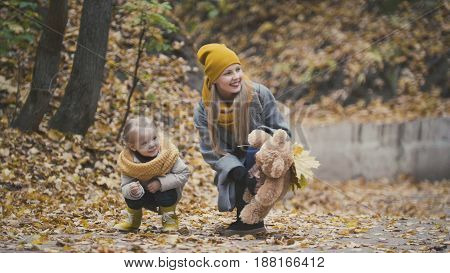 Little blonde girl with her mommy in autumn park - play and clap hands, close up, telephoto