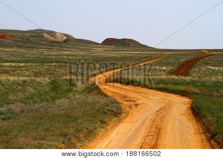 Steppe landscape with yellow country dirt road