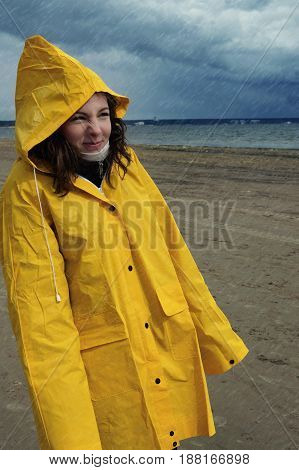 A Young Beautiful Girl In A Yellow Raincoat Is Standing In The Rain In The Spring On The Shore Of Th