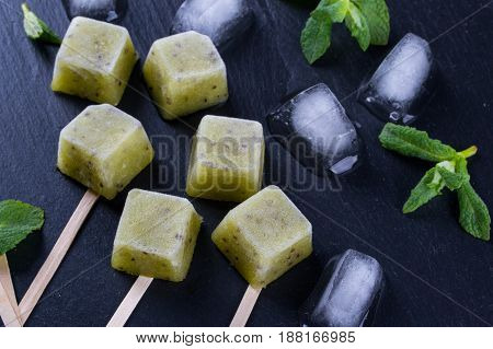 Homemade natural popsicles made with fresh kiwi with mint leaves. Summer Ice Cream, fruit dessert on  the black slate board