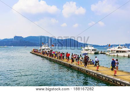 NANTOU TAIWAN - MAY 06: This is a view of a pier with tourists and tourboats on Sun Moon Lake a famous travel destination on May 06 2017 in Nantou