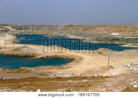 Gypsum quarry with white plaster material and flooded mines
