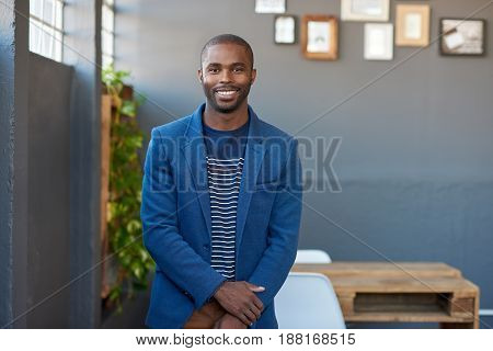 Portrait of a young African businessman in a blazer smiling confidently while standing alone in a large modern office