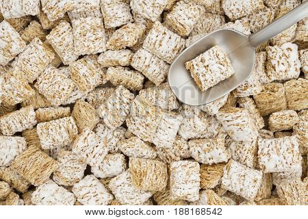 Whole grain wheat cereal with a spoon for a healthy cereal background