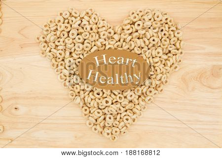 Cereal is a healthy snack Healthy oats cereal in the shape of a heart on wood with text Heart Healthy
