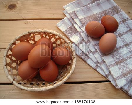 Eggs in a wicker basket and on a kitchen towel.