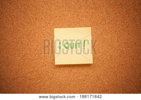 Close up image of a sticky note reading 'I quit' on a cork board.