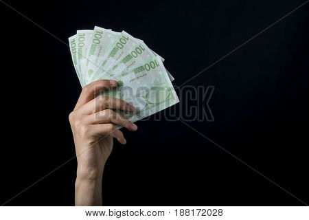Isolated 100 Euro Cash Holding On A Black Background.
