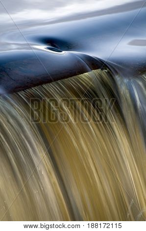 Whirlpool swirling near edge of small spillway