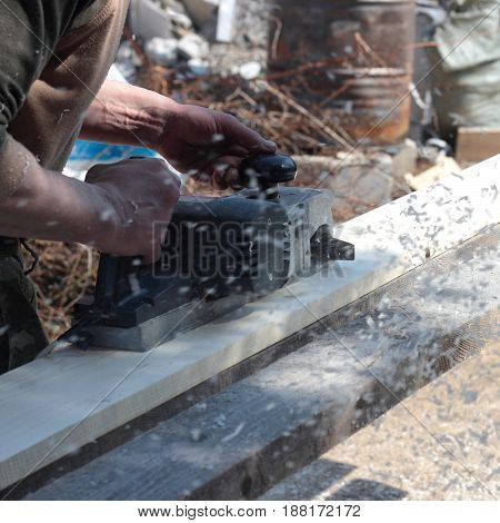 Construction repair tools - Electric hand plane during processing of boards.
