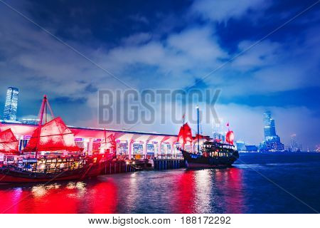 HONG KONG CHINA - APRIL 25: Night view a pier in Victoria harbor with traditional Chinese sailboats which are popular with tourists on April 25 2017 in Hong Kong