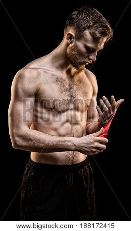 Fighter man with boxing bandages on black background