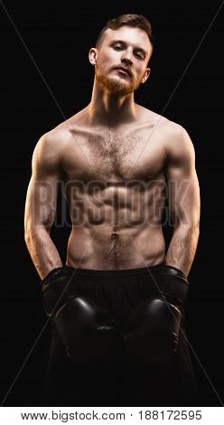 Bearded athlete with boxing gloves on black background