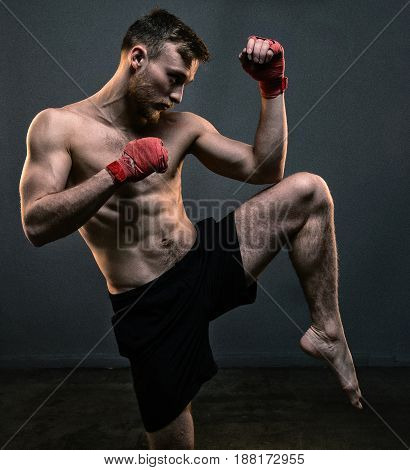 Bearded fighter during hard workout on black background