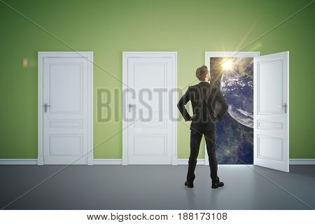 Back view of young businessman in green interior looking out of open door with space view. Success concept. 3D Rendering
