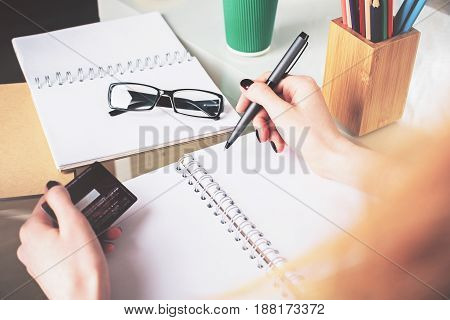 Woman Copying Information From Card