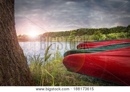 Canoe boats near a river sunrise in background.