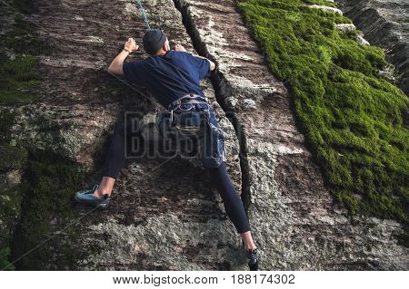 Rock climber. is engaged in rock climbing with insurance on rocks with green moss