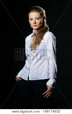 young woman wearing white shirt, black trousers and black bow-tie isolated on black background