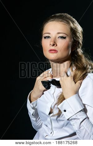 young sexy female in white shirt and black bow-tie isolated on black