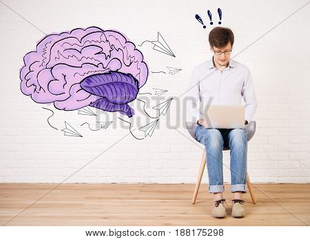 Young businessman sitting on chair and using laptop in bright interior with brain sketch on wall. Creative mind concept