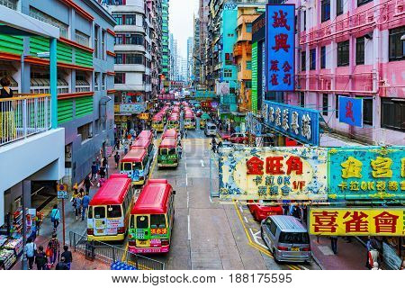HONG KONG CHINA - APRIL 24: This is a view of a local bus station in Mongkok on a busy street with signs and typical Hong kong architecture on April 24 2017 in Hong Kong