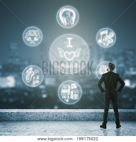 Back view of young businessman standing on rooftop with digital chart and night city view. Music concept