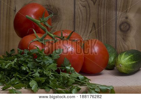 Red tomatoes with cucumbers and parsley are excellent ingredients for cooking salads