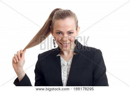 Portrait of sexual young blonde who is smiling looks into the camera and holds hand ponytail isolated on white background