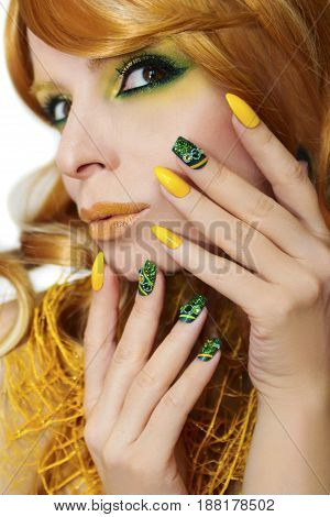 Green yellow makeup and manicure with rhinestones,sparkles on the sharp and square shape nail girls with red hair on a white background.Nail art.