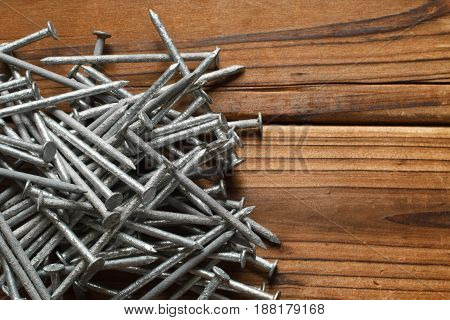 Galvanized carpentry nails on wood. Top down view.